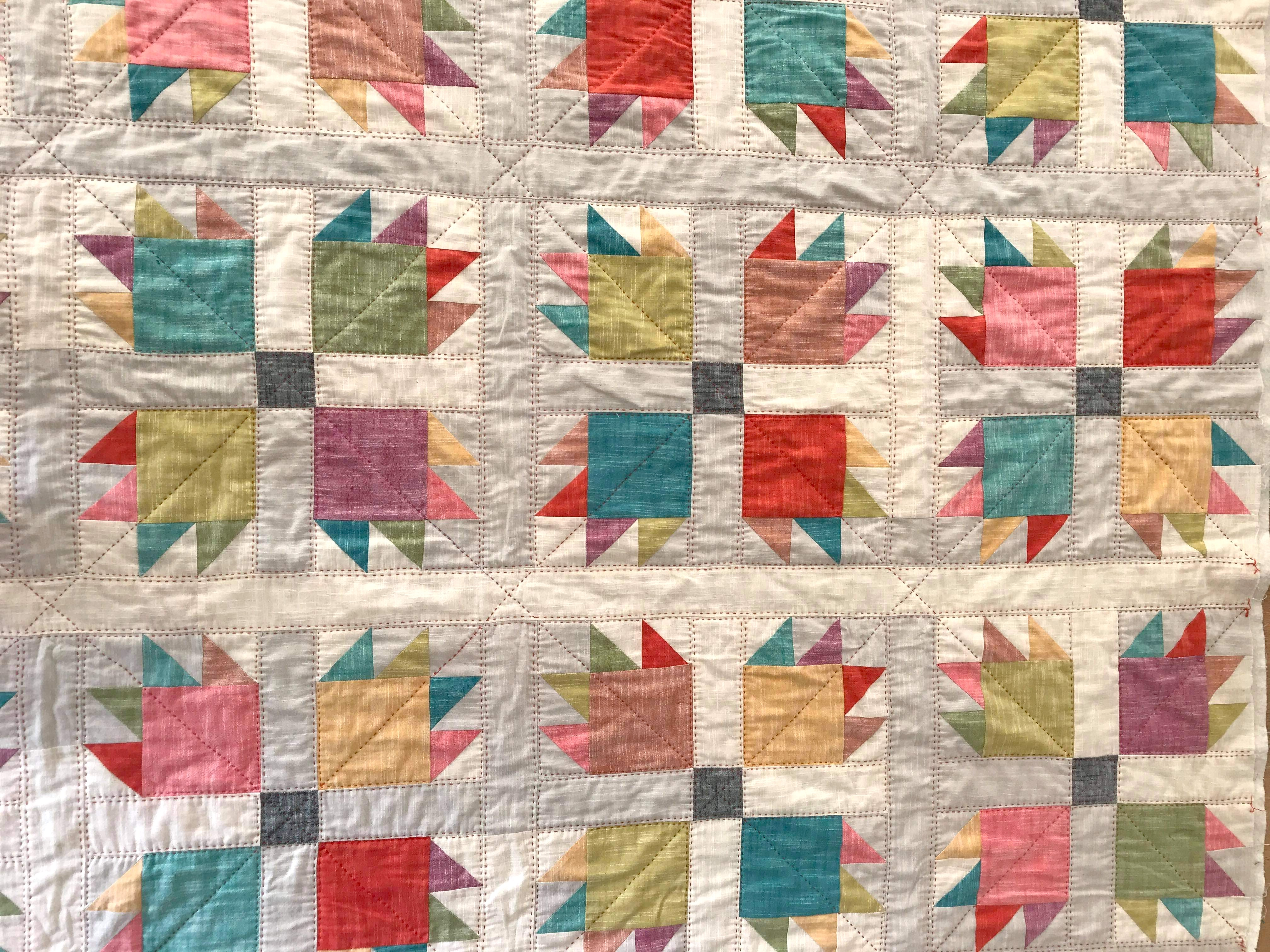 A bear paw quilt in a bright mix of solid Manchester fabrics, made by Sandra Dorse